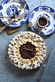 Chocolate banana cream pie on a pan with blue plates and cutlery