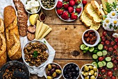 Olive tapenade, sausages, baby corns, french baguette, cheese, capers, strawberries, corn bread slices, sun-dried tomatoes, cherry tomatoes and cucumber slices on a wooden board