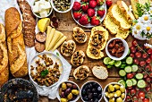 Olive tapenade spread on bread slices served on a wooden board, French baguette, sausages, baby corns, cheese, strawberries