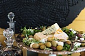 A cheese platter with olives and rosemary