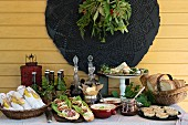 A summer buffet with mediterranean starters and dips, and a basket with rolled napkins