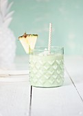 A pale green pineapple smoothie in a glass
