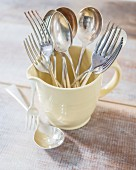 Silver forks and spoons in retro milk jug on rustic wooden table