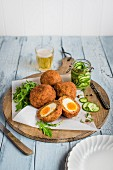 Scotch eggs with chorizo, peppers and cucumber relish