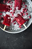 Raspberry ice lollies on sticks in an ice bucket