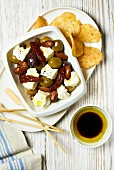 Feta with pickled olives, dried tomatoes, potato chips and olive oil