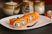 Salmon sushi with fresh cheese on a serving platter
