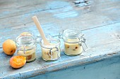 Apricot and quark pancakes baked in glass jars on a blue wooden table