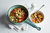 Bean stew with red and yellow pepper, olives and chorizo