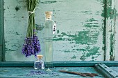 Glass bottle of lavender oil, bunch of lavender and dried lavender blossoms