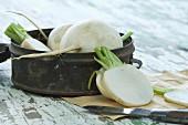 Rettiich halbiert und Scheiben mit Messer und Blechdose auf Holztisch