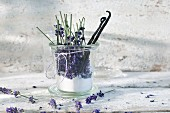 Glass of lavender sugar with avender blossoms and vanilla beans