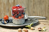 Glasses of chia pudding with different berries, pomegranate seeds and hazelnuts