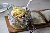 Swiss sausage salad in a glass jar with buttered bread
