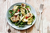Salad with spinach, grilled zucchini, spring onion on plate, vegan