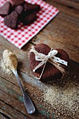 Stack of heart-shaped chocolate shortbreads tied with lace and tea spoon of brown sugar on wood