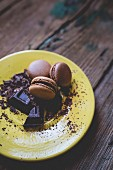 Different macarons and chocolate shaving on yellow dish
