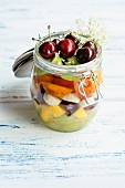 Fruit salad in jar with grapes, mango, banana, cherries, apricot, kiwi, garnished with elder flowers