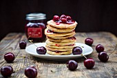 Stack of American pancakes with cherries and cherry groats