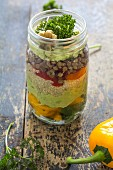Glass of salad with lentils, quinoa, avocado, vegetables and walnuts