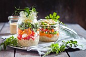 Rainbow salads in jars, quinoa, carrots, peas, red cabbage, bell pepper, mung bean sprouts, the other with tomatoes, mozzarella, spinach, pea sprouts