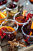 Sangria with cinnamon, orange, berries in a glass with sugar