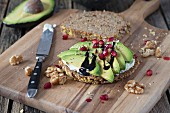 Protein bread slice with cream cheese, sliced avocado, walnuts and pomegranate seed on wooden board