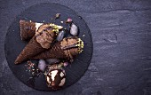 Chocolate ice creams with pistachios melting on dark background with empty space