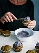 Frosting being spread onto green oat and blueberry muffins with a knife
