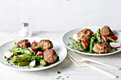 Fried meatballs with green asparagus and radish salad