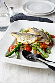 Fried gilthead bream fillets on a bed of green asparagus with tomato sauce