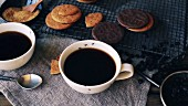 A drop falling into a cup of coffee, with cookies on a cooling rack in the background