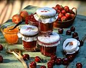 Kirschmarmelade in mehrere Gläsern und Aprikosenmarmelade