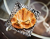A croissant on a silver plate (top view)