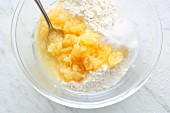 Tinned pineapple, baking powder, sugar and flour being mixed together in a bowl