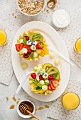 A healthy breakfast: fruit salad served in melon halves, yoghurt, granola, orange juice and honey