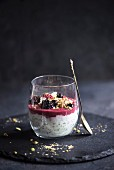 Chia pudding topped with cereal and a berry smoothie in a glass