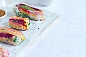 'Rainbow' raw vegetable summer rolls with peanut and orange dip
