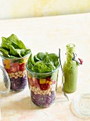 Brightly coloured layered salad in a glass with avocado dressing