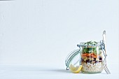 Barley salad with aubergine and feta in a glass jar