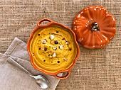 Pumpkin soup with hazelnuts in a pumpkin-shaped soup tureen