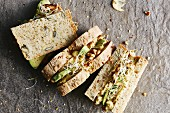 Sandwiches on seed bread with apple and chickpea spread, avocado, alfalfa sprouts and walnuts