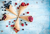 Various berries and cherries in ice cream cones