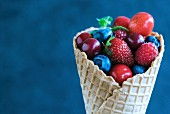Fresh berries and cherries in an ice cream cone