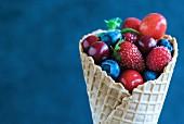 Fresh berries and cherries in an ice cream cone