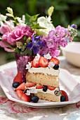 Ein Stück Victoria Sponge Cake mit Beeren auf Tisch im Freien