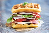 A waffle sandwich with ham, tomato, mozzarella and rocket