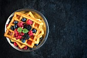 Belgian waffles with fresh berries on a plate (seen from above)