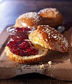 A brioche, sliced open, with coarse sugar crystals and raspberry jam