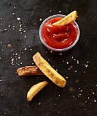 Four French fries on a black baking tray with tomato ketchup